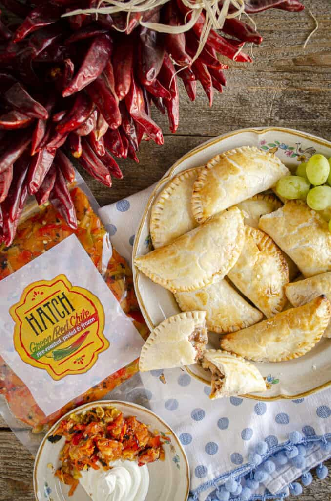 Make the Best Baked Empanadas with Hatch Chile Beef Filling. Empanadas on a plate next to a red chile ristra and a package of Hatch Chile.