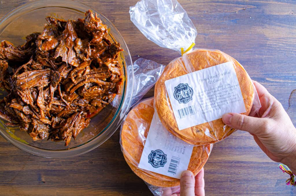 A person holds two packages of special red chile corn tortillas next to a bowl of shredded Birria beef.