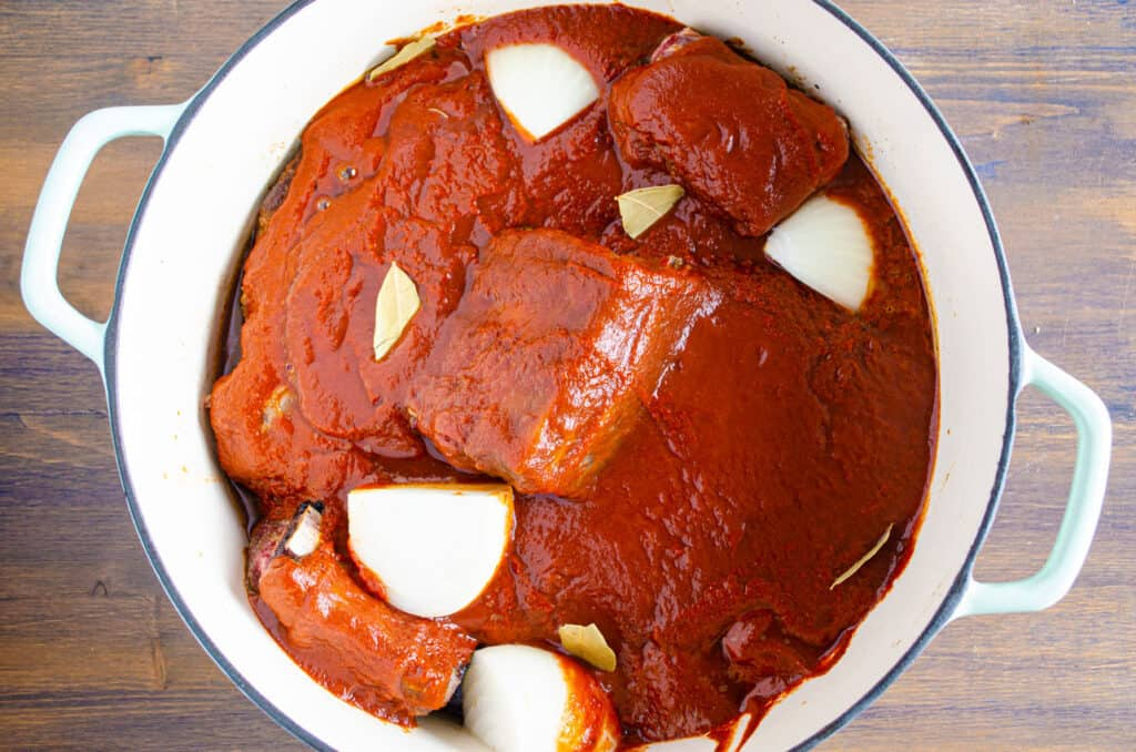 Looking down into a pot filled with beef chunks smothered in red chile sauce. Large chunks of onion and small bay leaves are scattered around on top.