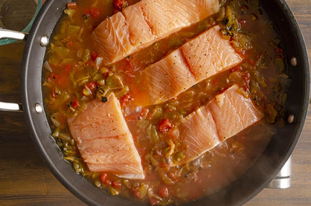 Looking down into a large non-stick skillet filled with salsa and raw, pink, salmon fillets placed skin side down (skin not visible).