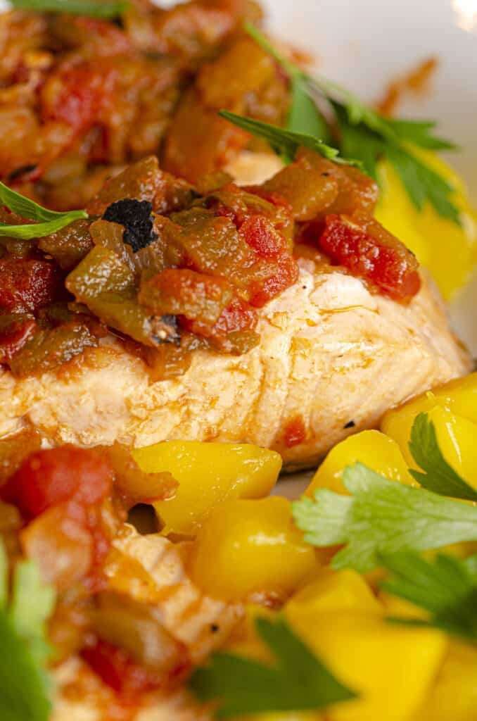 An extreme closeup of a serving of Easy, One-Pan Salsa Poached Salmon with Mango showing the texture of the cooked fillet, along with the tomato and green chile chunks in the salsa. The fish is garnished with chunks of fresh yellow mango and a sprinkle of green parsley.