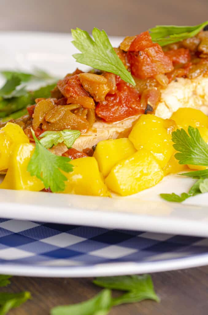One fillet of Easy, One-Pan Salsa Poached Salmon with Mango sits on a white plate. The top of the fillet is smothered in chunky salsa. Mango chunks surround the salmon.