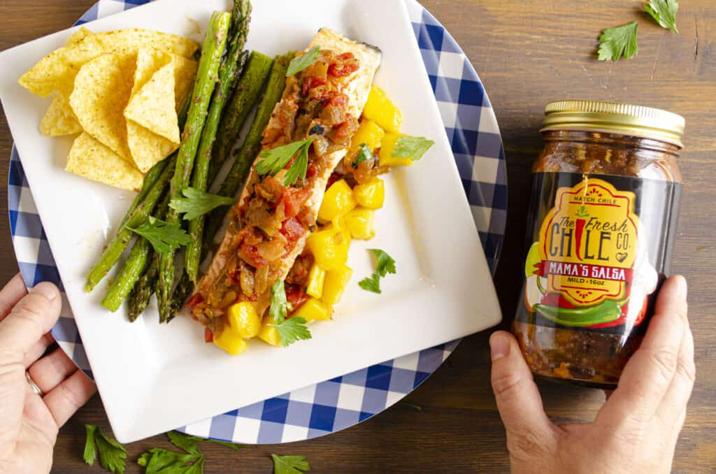Looking down on a white square plate on a wooden table top displaying a serving of Easy, One-Pan Salsa Poached Salmon with Mango with grilled asparagus, mango chunks and tortilla chips. A person holds a jar of The Fresh Chile Co.'s Mama's Salsa next to the plate.
