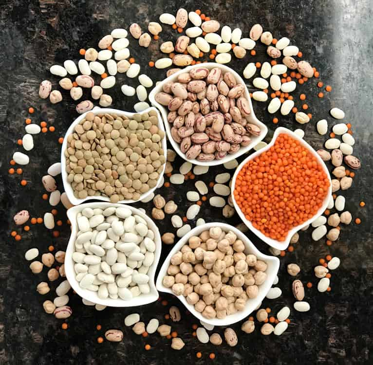Stylized white bowls on a black stone table are filled with various kinds and colors of dry beans and lentils.