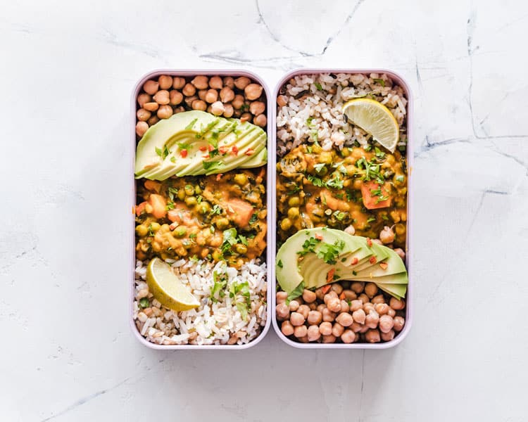 Rectangular meal prep containers on a white marble table hold prepared chickpeas, lentil stew, rice and sliced avocado.